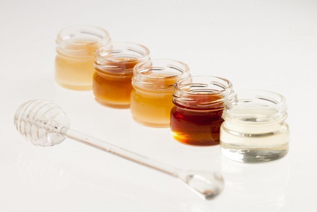 4 frascos con distintas mieles y palito